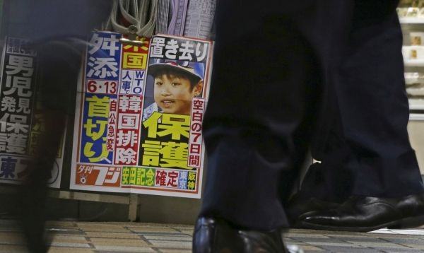 An image of Yamato Tanooka, the missing 7-year-old Japanese boy, is displayed by Japanese newspaper Yukan Fuji being sold at a railway station kiosk in Tokyo, Friday, June 3, 2016. Tanooka, who went missing nearly a week ago after his parents left him in a forest as punishment, was found Friday in a case that set off a nationwide debate about parental disciplining.(AP Photo/Shuji Kajiyama)